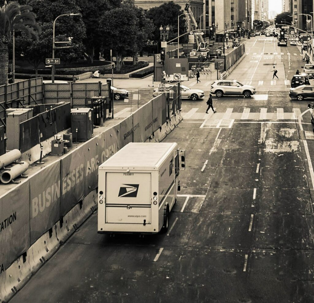 A photo of a mail truck driving down a city street